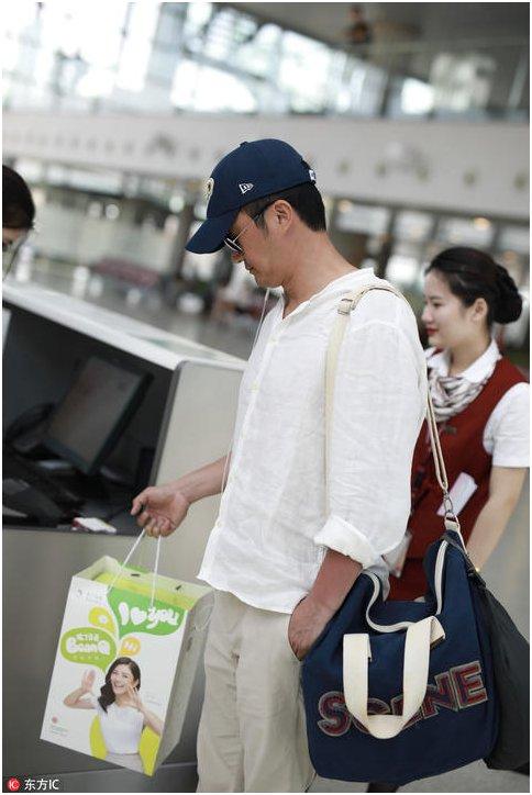 吴京现身机场被拍 再忙也要给孩子带礼物